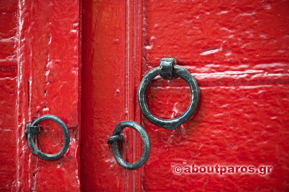 An old red door in a settlement of Paros